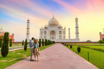 Wall Mural - Taj Mahal white marble mausoleum at sunset with view of tourist couple enjoying the sunrise view at Agra, India