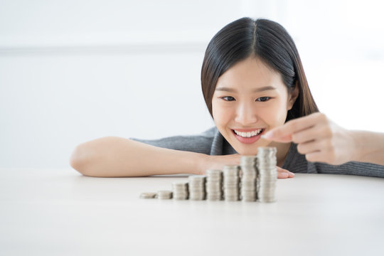 Young Asian woman making stack of coins. invest save finance concept.