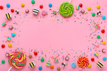 festive wreath background with assortment of colourful caramel candies with jelly and sprinkles over pink and space for your greetings