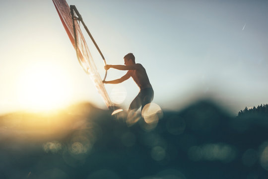 Low angle splashing view of windsurfer sailing on windsurf board