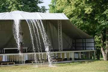 rainwater is pushed from a canopy above the stage before the festival begins