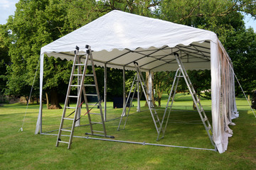 event tent set up  with ladders on the lawn in a park for a summer party or wedding