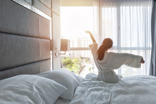 Hotel room comfort with good sleep easy relaxation lifestyle of Asian girl on bed have a nice day morning waking up, taking some rest, lazily relaxing in guest bedroom in city hotel