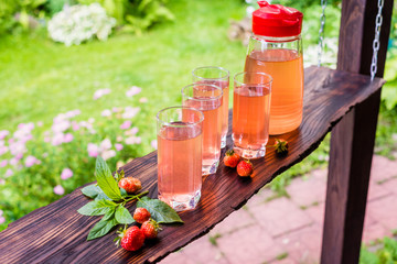 Four full glasses and jug of fruit juice. Strawberries and mint. Summertime.