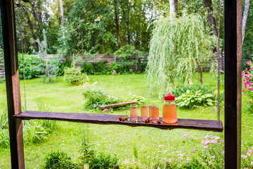 Long wooden table with four full glasses and jug of fruit juice on terrace. Summertime in countryside.