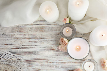 Acrylic Prints Relaxation Flat lay composition with burning aromatic candles and roses on wooden table. Space for text