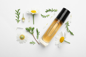 Composition with chamomile flowers and cosmetic bottle of essential oil on white background, top view Wall mural