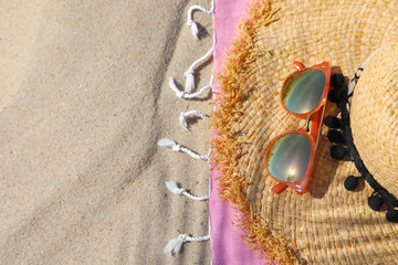 Flat lay composition with beach accessories on sand. Space for text