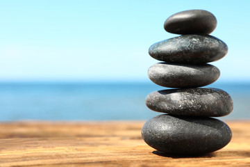 Stack of stones on wooden table against seascape, space for text. Zen concept
