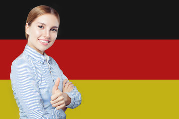 Travel in Germany concept. Pretty busineswoman showing thumb up against the Germany flag background