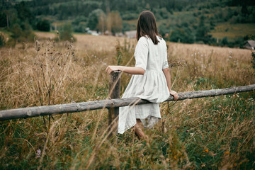 Stylish girl in linen dress sitting on aged wooden fence among herbs and wildflowers, looking at field. Boho woman relaxing in countryside, simple slow life style.  Atmospheric image