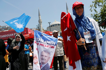 AKP supporters wave party flags and a flag with pictures of  their mayoral candidate Yildirim at an election kiosk in Istanbul