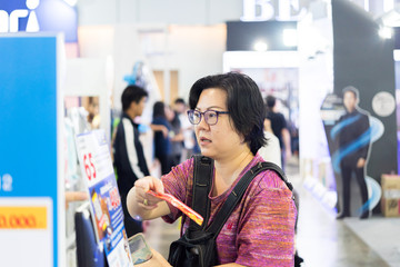 Asian woman with shopping cart in department store