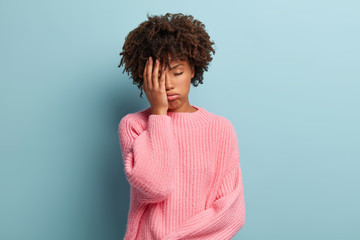 Beautiful overworked woman feels sleepy, covers half face with palm, keeps eyes closed, sighs from tiredness, wears pink sweater, isolated on blue background. Negative feelings and boredom concept
