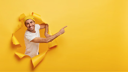 Smiling young handsome man stands in paper hole, points at free space, advertises or shows way, wears white t shirt, suggests going there, yellow background, has nice offer or gives opportunity