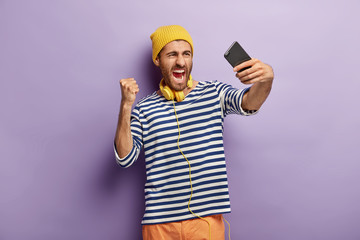 Discontent emotional angry man takes selfie picture, expresses negative emotions on camera, raises clenched fist, wears yellow hat and striped jumper, isolated on purple background, uses headphones