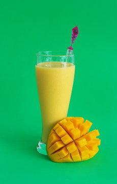 Mango milkshake and mango fruit on green background