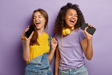Optimistic pleased mixed race women sing favourite song in smart phones, have fun and enjoy music,...