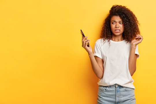 Beautiful female with frizzy Afro hairstyle, looks in displeasure at cell phone, receives call from former boyfriend, holds mobile phone on distance, ignores communication, afraids of something