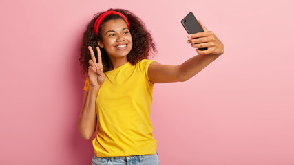 Lovely young curly female poses in smartphone camera, makes peace gesture, takes photo for social networks, enjoys free time, dressed casually, being on way to shop, isolated on pink background