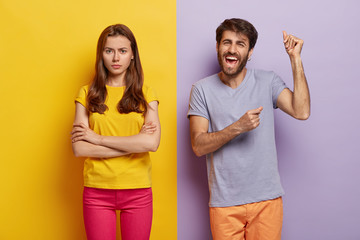 Happy cheering guy raises hands and dances happily, dissatisfied woman doenst pay attention to him, keeps hands crossed, angry after quarrel. Two colored background. People, facial expressions concept