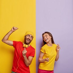 Positive couple listen music together, dance and move actively, being in good mood. Cheerful man in...