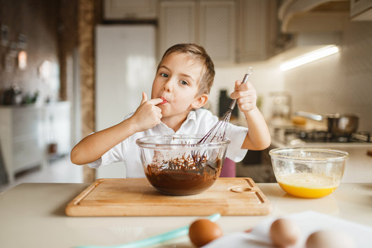 Male kid tastes melted chocolate in a bowl