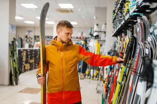 Man at the showcase choosing downhill ski