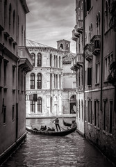 Fototapete - Venice in black and white, Italy. Old narrow street with lone gondola in the distance. Romantic water trip across vintage Venice canals. Concept of travel and vacation in the bizarre Venice city.