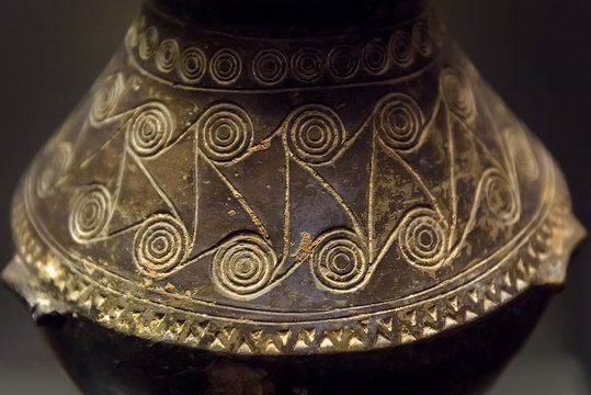 Ancient Greek pot, old patterned vase close-up. Archeological pottery with carved ornament.