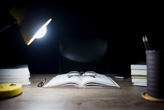 Reading table at night, Open books and glasses placed, Book Division and lighting lamps, Close-up on glasses.