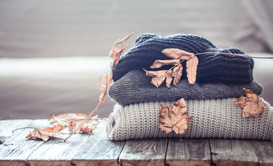 Stack of knitted sweaters on a wooden table Wall mural