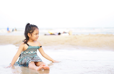 Asian child cute or kid girl smiling and enjoy or cheerful on beach or island and playing sea water or wave with sand alone on vacation travel for summer holiday relax with happy fun with copy space