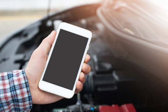 close up young business man hand using a mobile smart phone call a car mechanic ask for help assistance because car broken on the roadside. blank if empty screen.