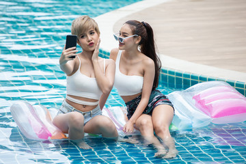 two Young asian women friends selfie on Inflatable air mattress in swimming pool