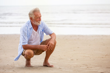 Senior man sitting on beach relaxing . Happy retired man relaxed on sand outdoors