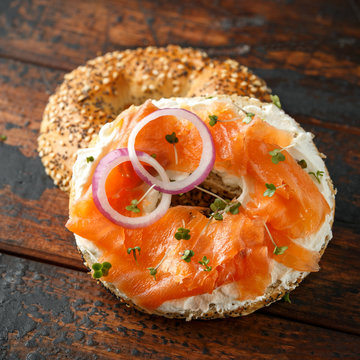 Bagels breakfast sandwich with Cream cheese and salmon on wooden table
