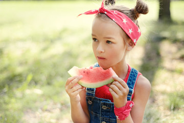 little girl eat watermelon. child in a red bandana with tails