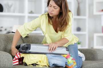 woman struggling packing suitcase at home