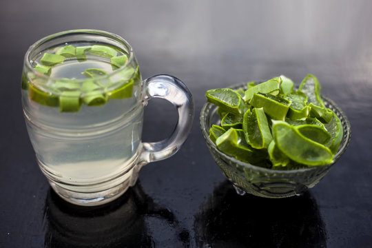 Close up of glass mug on wooden surface containing aloe vera detox drink in along with its entire raw ingredients with it. Horizontal shot with blurred background.