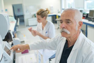 Photo sur Aluminium Pharmacie senior doctor examines a medical record in the hospital room