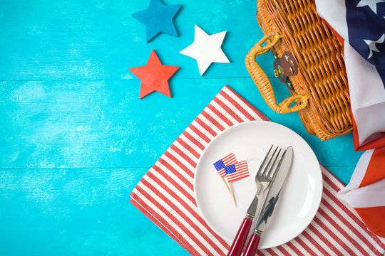 Happy Independence Day, 4th of July celebration concept with picnic basket, plate and USA flag on wooden background.