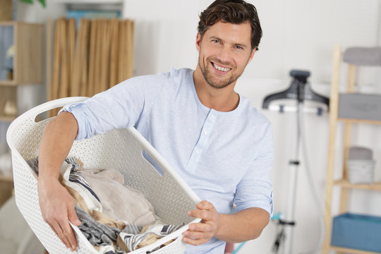elegant man with a laundry basket full of clothes
