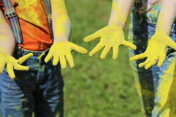 Poster children on holiday painting each other with colours, blue hair, yellow hair and hands on nature background