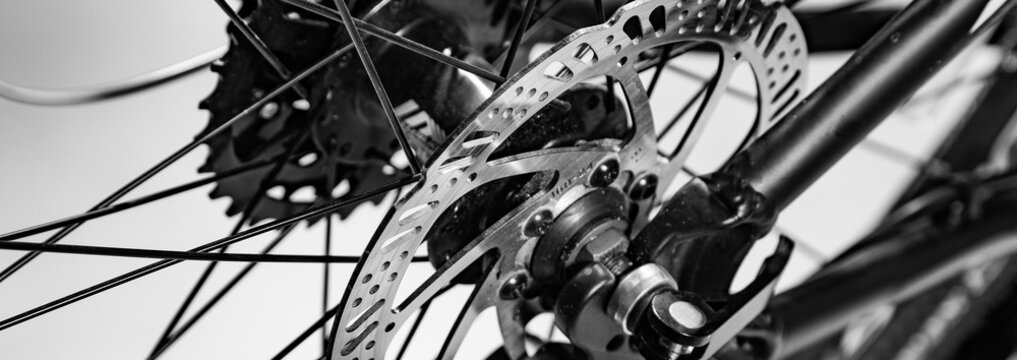 close-up shot of named mechanic brake disc on bicycle in black and white