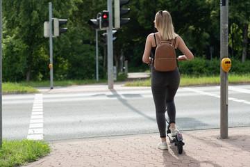 Junge frau mir e-scooter auf radweg an kreuzung mit ampel