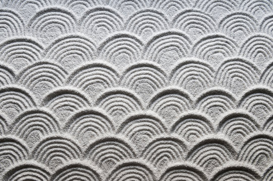 Graphic wave patterns raked into the white sand of a Japanese Zen garden for a full frame background of tranquility