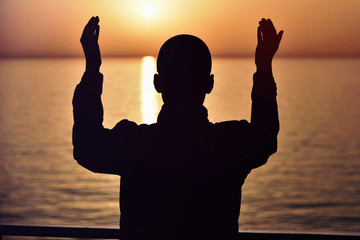 Muslim prayer in the ship praying at sunset with hands up. A silhouette of islamic praying at...