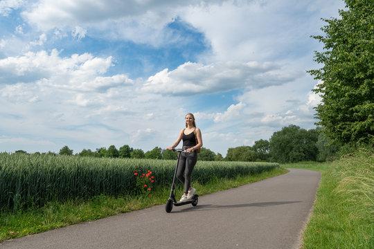 Junge Frau fährt Elektroroller auf Radweg in der Natur