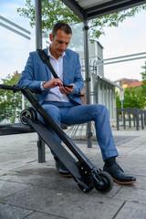 Mann wartet mit e-scooter an Haltestelle und liest Nachricht